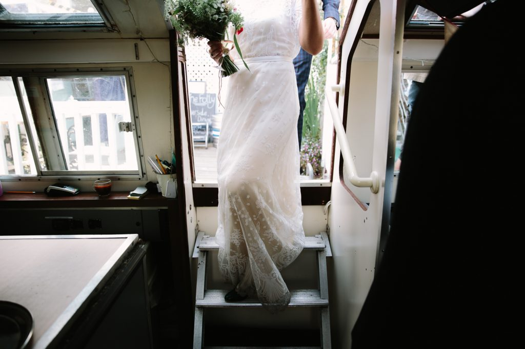 a bride getting onto a riverboat in oxford. Her and all her guests will be travelling from The Folly Restaurant to The Perch to continue their wedding day