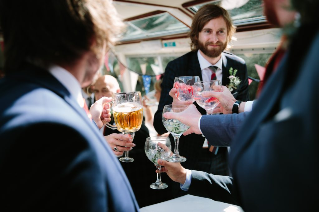 Guests cheering the wedding party with their drinks on a river boat on the Thames in Oxford.