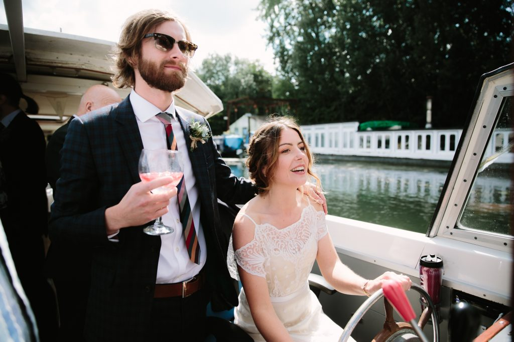 A bride driving a riverboat up the River Thames in oxford to The Perch to enjoy the rest of her wedding.