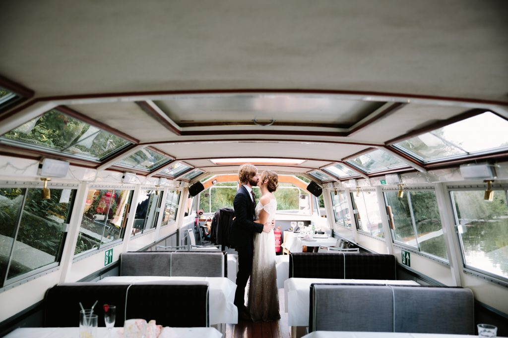 A stunning bride and groom kissing on a riverside boat outside The Perch in oxford.
