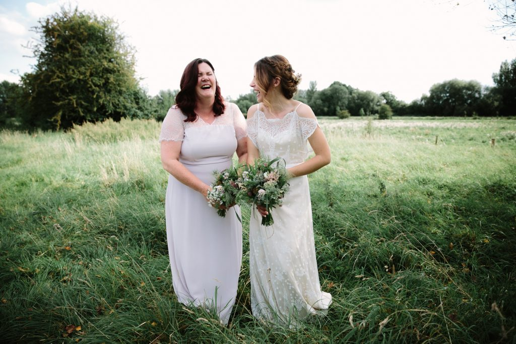 Bridesmaids in Port Meadow in Oxford, wearing vintage dresses, giggling