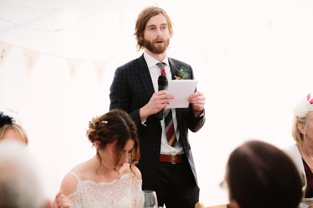 A groom giving a speech at an Oxford Garden Wedding. The bride wears her vintage white dress sits next to him. Happy tears run down her face