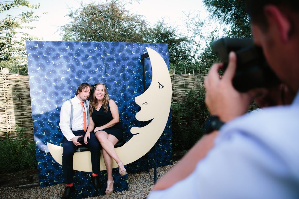a homemade Photo Booth at an oxford wedding. A blue background and a moon, then a couple sit on the moon and the person takes a photo using a poloriod camera