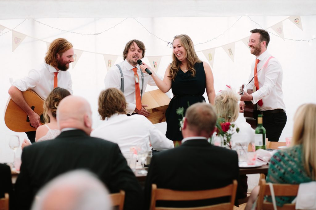 Best man giving a speech and playing the guitar to a bride and groom in a marquee wedding in oxfordshire