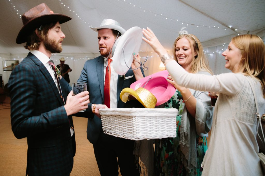 Sharing cowboy hats for everyone to wear at an oxford wedding.