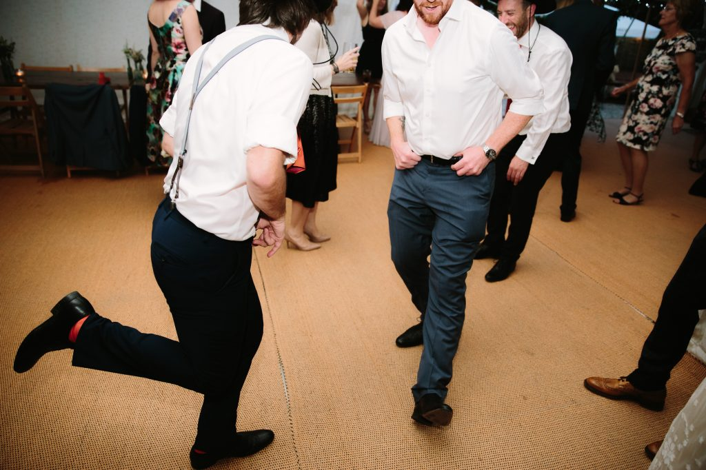 Guests dancing at a wedding in oxford. Boys kicking their feet to the beat in a marquee in the garden of The Perch Inn.