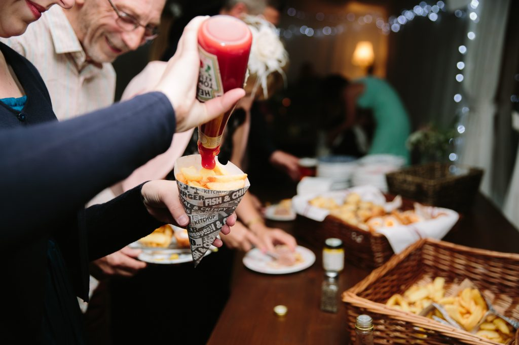 Chips being served at the end of a wedding in Oxford. The perch Inn providing all the food, happy faces putting ketchup onto their chips