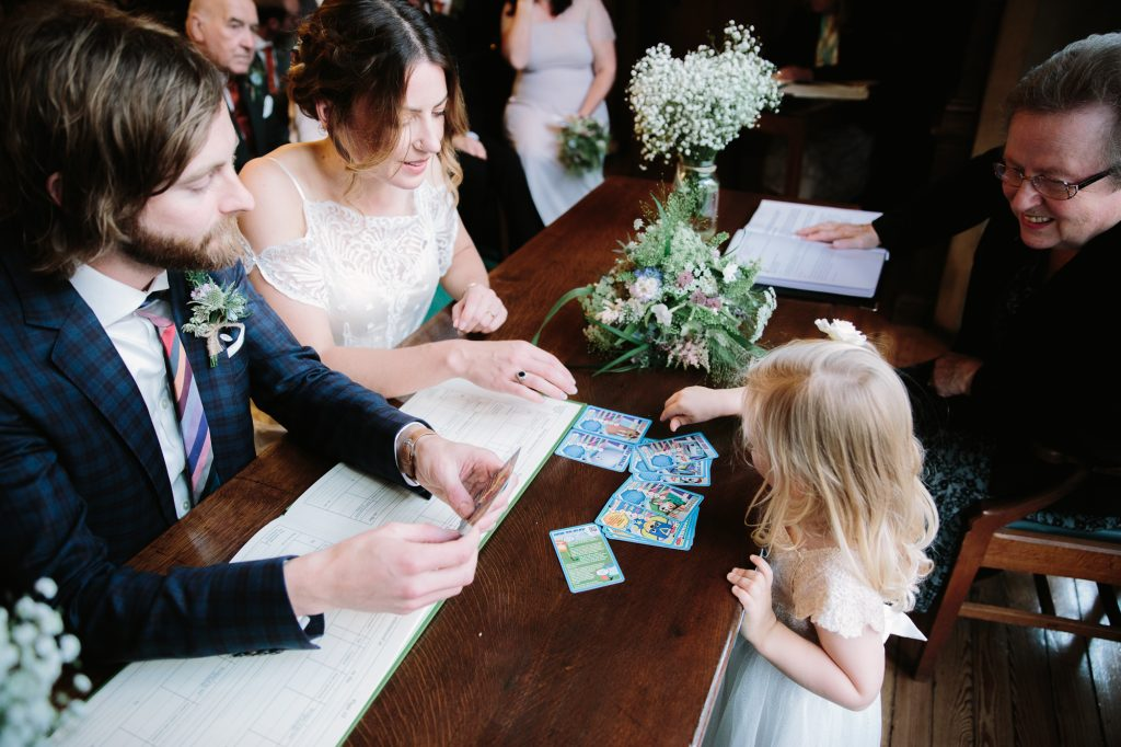 A flower girl playing cards with the bride and groom in oxford town hall