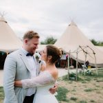 Alternative Wedding Venues in Oxfordshire - Bride and Groom standing in front of tipi
