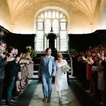 OXFORD CITY WEDDING VENUES - Bride and Groom walking out of Bodlien Library after getting married