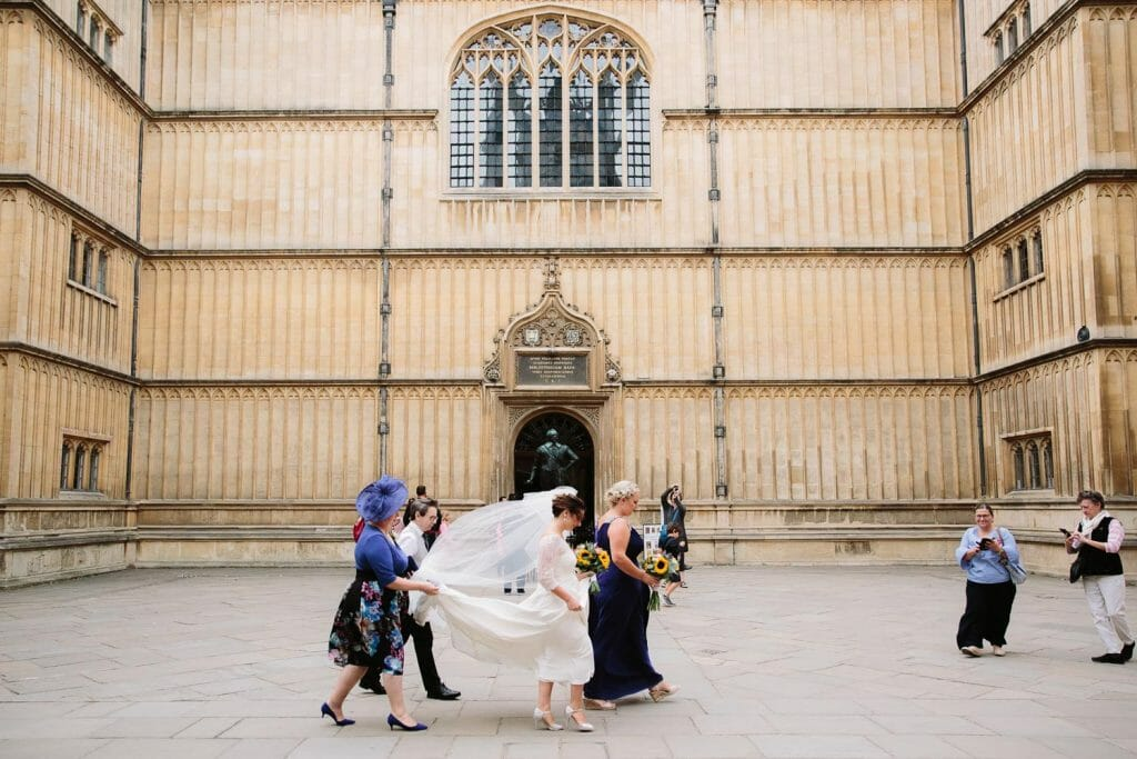 Bodleian Library Wedding Photographer - bride walking through the quod